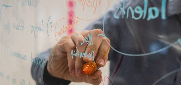 Mies piirtää taululle. Photo by Kvalifik on Unsplash