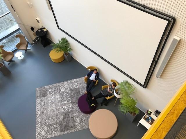Kuvassa opettajien yhteissuunnittelutila, jossa valkokangas, nojatuoleja, kasveja.